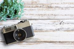 Office desk wooden table with vintage camera and fresh flower. Top view with copy space. Top view of old camera over white wood table. Retro vintage filter Royalty Free Stock Photo