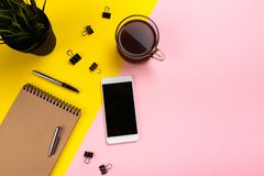 Office desk working space - Flat lay top view of working space with white blank notebook, earphone, coffee cup and mock up phone stock photos