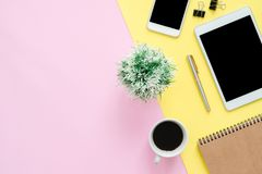 Flat lay top view of working space with blank notebook page, coffee cup and mock up phone tablet on pastel background. Office desk working space - Flat lay top royalty free stock image
