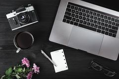Office desk workplace. Cup of tea or coffee, photo camera, laptop computer, eyeglasses and green pink plant on old wood table. Top. View, flat lay Royalty Free Stock Photos