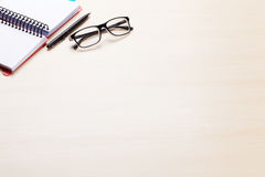 Office desk workplace with notepad and glasses Stock Photos