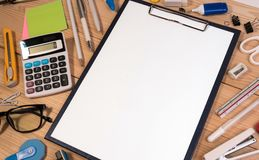 Office desk workplace with office or school supplies with blank paper in the center. Stock Photos