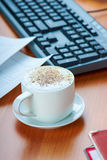 Office desktop with cappucino coffee cup and work essential tools Royalty Free Stock Photos