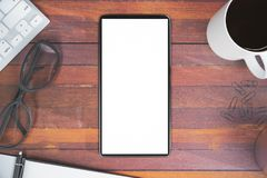 Office desktop with cellular phone. Top view of wooden office desktop with blank white cellular phone, coffee cup, keyboard, glasses and other items Royalty Free Stock Image