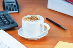 Office desktop with coffee cup and work essential tools Royalty Free Stock Image