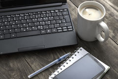 Office desktop with coffee, notepad and laptop. Royalty Free Stock Photography