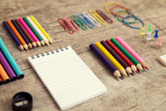 Office desktop with colorful pencils, notepad, supplies and pape Royalty Free Stock Image