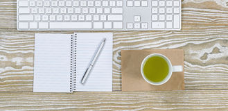 Office Desktop with Green Tea Drink. Top view shot of an old white desktop with keyboard, green tea in cup, notepad and pen in horizontal format Stock Images
