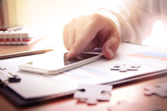 Office desktop with hand using mobile phone, paperwork, stationary and puzzle pieces Royalty Free Stock Photos