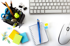 Office desktop. With keyboard, mouse, notebook and basket of writing tools Stock Photo