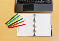 Office desktop with laptop, opened notebook and pencils. Office desktop with laptop, opened notebook and colorful pencils Royalty Free Stock Photo