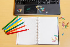 Office desktop with laptop, opened notebook and pencils. Office desktop with laptop, opened notebook and colorful pencils Royalty Free Stock Image