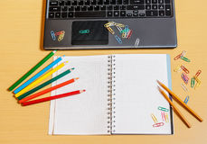 Office desktop with laptop, opened notebook and pencils Stock Photo