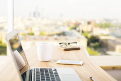 Office desktop side. Side view of office desktop with laptop, coffee cup, smart phone, glasses and other items on blurry city background Stock Photo