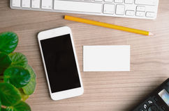 Office desktop with smartphone, computer and blank business card, top view Stock Image