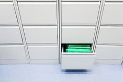 Office document storage furniture. Grey closed all except one in the middle right royalty free stock photo