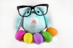 Office Easter. Blue Easter bunny rabbit with black eyeglasses and easter colorful  eggs Stock Images