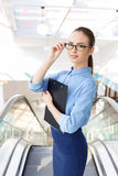 Office employee with clipboard fixes her glasses. Ready to generate. White collar worker with clipboard is ready for working process Stock Photos