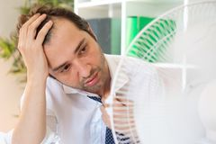 Businessman trying to refresh at work in summer heat. Office employee feeling stressed after summer heat haze Royalty Free Stock Photography