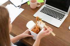 Office employee having noodles for lunch at workplace, closeup. Food delivery stock photo
