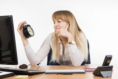 Office employee sadly looks at the clock with time nine oclock five minutes in the morning Royalty Free Stock Photos