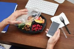 Office employee with smartphone having lunch at workplace. Food delivery. Office employee with smartphone having lunch at workplace, closeup. Food delivery stock image