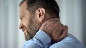 Office employee suffering from neck pain, working in front of computer, spasm royalty free stock photo
