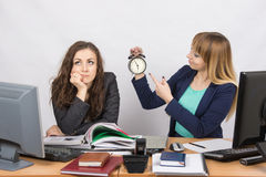 Office employee working at the end of the day, one with a smile, indicating the clock, the other thoughtfully props head Stock Image
