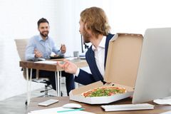 Office employees having lunch at workplace. Food delivery royalty free stock photography