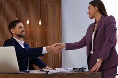 Office employees shaking hands over table with documents stock photography