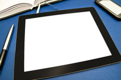 Office equipment. A tablet with blank white screen, a mobile phone, a calendar and a pen on blue background Stock Photo