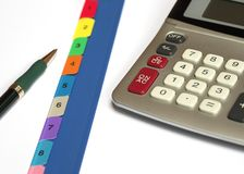 Office Equipment. Some office equipment including ballpoint pen, calculator and file with numbered inserts royalty free stock photography