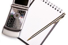 Office equipment concept - spiral notebook, pen and modern phone Stock Photos