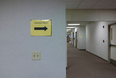 Office Evacuation Route. Yellow sign with arrow pointing the way for office building evacuation Royalty Free Stock Photography