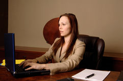 Office Executive Typing. Female corporate executive typing on a laptop at her desk stock image