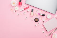 Office feminine desk with laptop, notebook, cosmetics and flowers on pink background. Top view. Flat lay concept. Office feminine desk with laptop, notebook Stock Photo