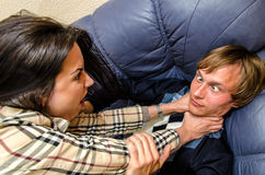 Office fight. Woman trying to stifle a men on the sofa Royalty Free Stock Photography