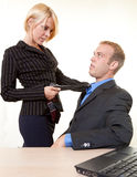 Office flitation. Business man sitting down with a business woman standing with a knee on his chair pulling on his tie Stock Photography