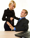 Office flitation. Business man sitting down with a business woman standing with a knee on his chair pulling on his tie Stock Photo