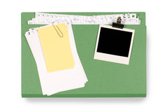 Office file folder untidy torn notepaper and yellow post-it style sticky note, blank polaroid photo frame. Office folder with untidy note paper and blank Royalty Free Stock Image