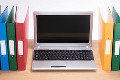 Office folders and open laptop computer on desk stock image