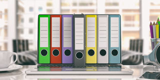 Office folders out of a laptop - office background. 3d illustration. Colorful ring binders out of a laptop screen in an office. 3d illustration Royalty Free Stock Photography