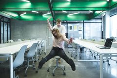 A man rides a girl on a chair at the office. Entertainment in the office.Break at work stock photos