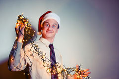 Office funny man in a Santa Claus red cap with yellow garlands. Corporate events concept Royalty Free Stock Photos