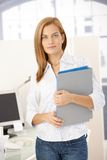 Office girl with folders. Portrait of office worker girl standing at desk with folders in hands, smiling at camera Royalty Free Stock Images