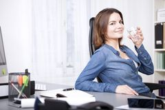 Office Girl at her Desk Holding a Glass of Water Stock Image