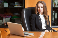 Office girl with laptop. Young beautiful girl sitting on the black leather chair looking into laptop display Stock Image