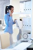 Office girl on phone call checking folders. Office worker girl on mobile phone call standing at shelf, checking folders Stock Photography