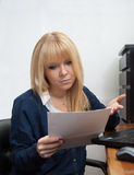 Office girl reads a letter looking worried Royalty Free Stock Image