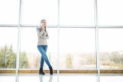 Office girl speak phone against big panoramic windows. Pretty office girl speak phone against big panoramic windows royalty free stock photo